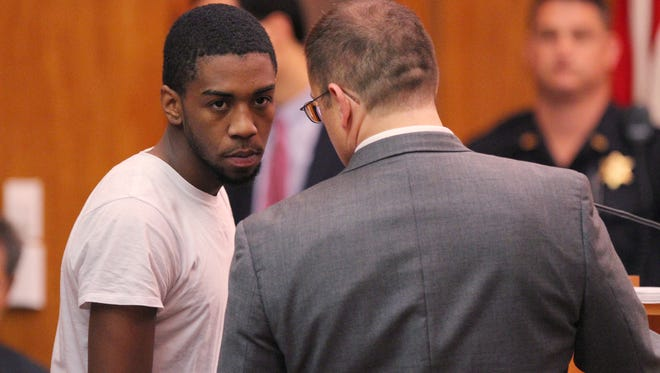 Jalen Everett bends forward while his lawyer whispers something to him during Everett's murder arraignment.