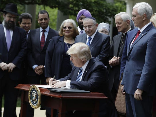 President Trump signs an executive order in the Rose