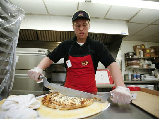 Kyle Brown prepares a taco pizza at the Casey's General