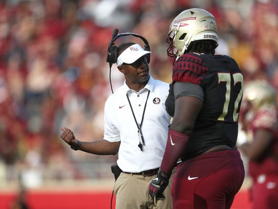 FSU Head Coach Willie Taggart talks to Mike Arnold