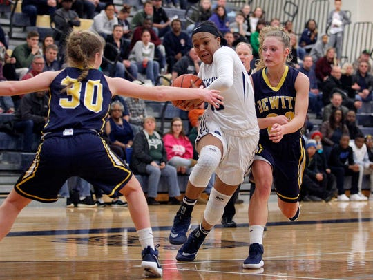 East Lansing's Jaida Hampton, center, drives for a layup between DeWitt's Lily Stephan, left, and Annie McIntosh, right, Friday, March 2, 2018, in Owosso, Mich. East Lansing won 50-38.