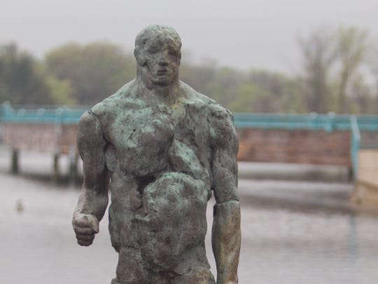 """The sculpture """"Decision Pending"""" is a lightning rod of opinion at the Brighton Mill Pond. Some call the artwork the """"Ugly Naked Guy."""""""