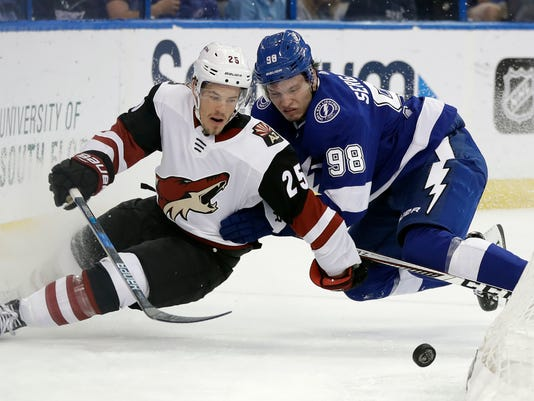 Arizona Coyotes center Nick Cousins (25) gets taken down by Tampa Bay Lightning defenseman Mikhail Sergachev (98) during the first period of an NHL hockey game Monday, March 26, 2018, in Tampa, Fla. (AP Photo/Chris O'Meara)