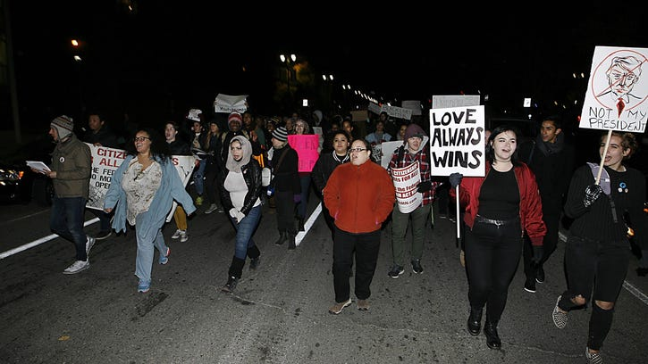 Protesters march down Anthony Wayne Dr. during a Rally & March To Shut Down Trump's Racist Vision For America! at WSU in Detroit, Friday, Nov. 11, 2016.