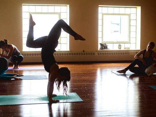 Majken Tranby, owner of Moodra yoga studio in South Hero, does a hand stand at the open posture session held at the conclusion of a class taught at Yoga Vermont in Burlington on Wednesday.
