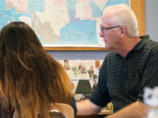 Teacher Mike King helps a student at the New Castle County Learning Center which is no longer open on Mondays due to recent budget cuts.