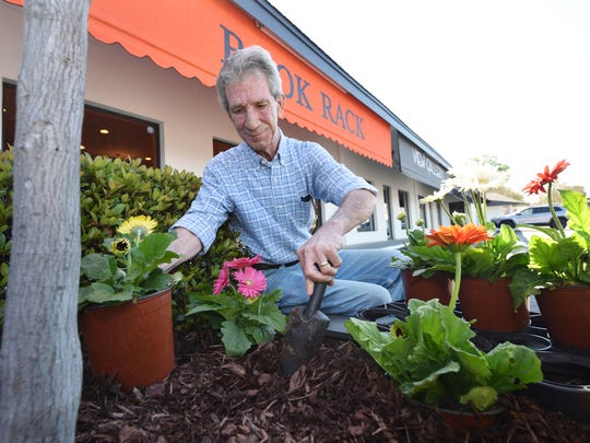 Property manager Steve Baker tends to a flower bed on Tuesday at Jackson's Canton Mart Square. The shopping center will celebrate 50 years of business Saturday.
