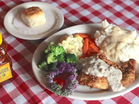 The chicken fried chicken dish at Rooster's Fried Chicken is topped with country gravy and served with mashed potatoes, a vegetable medley, and a biscuit.