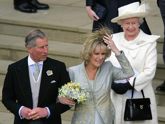 Queen Elizabeth II looks on as Prince Charles and his