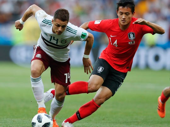 Mexico's Javier Hernandez, left, challenges for the ball with South Korea's Hong Chul during the group F match between Mexico and South Korea at the 2018 soccer World Cup in the Rostov Arena in Rostov-on-Don, Russia, Saturday, June 23, 2018. (AP Photo/Eduardo Verdugo)
