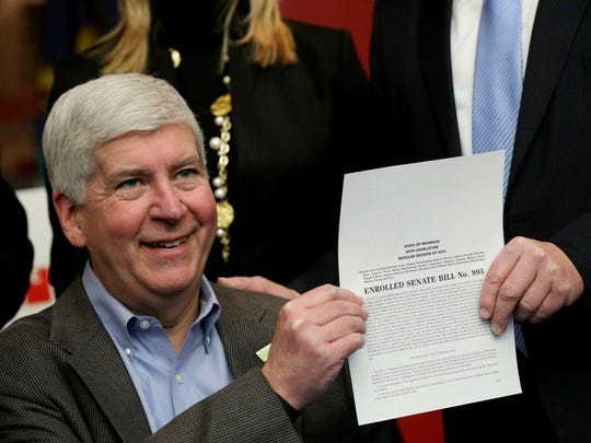 Gov. Rick Snyder poses for a photograph after signing legislation that establishes comprehensive regulations for the testing, use and eventual sale of autonomous vehicle technology at the Automotive Hall of Fame in Dearborn on Friday, December 9, 2016.