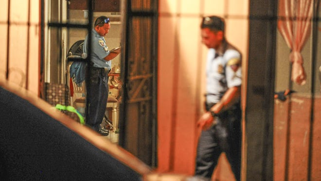 Officers with the Guam Police Department conduct an investigation of a reported assault on San Isidro Street in Agat on Wednesday, Sept. 16.