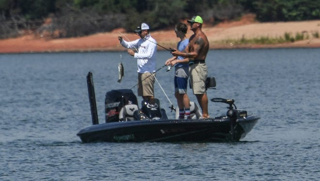 Brady Kimbrell, right, of Piedmont holds a largemouth bass near Tyler Owens, middle, and his father Travis Owens, both of Piedmont, during a fishing outing at Green Pond Boat Landing in Anderson on Tuesday.
