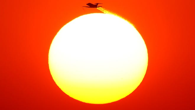 A jet takes-off from Sky Harbor international Airport and flies over the sun on the summer solstice on Jun. 21, 2017 in Phoenix, Ariz.