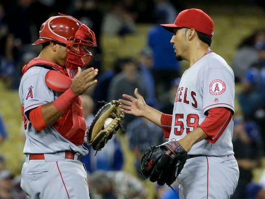 Los Angeles Angels relief pitcher Fernando Salas, right, and catcher Carlos Perez celebrate after their 7-6 win against the Los Angeles Dodgers during a baseball game in Los Angeles, Monday, May 16, 2016. (AP Photo/Chris Carlson)
