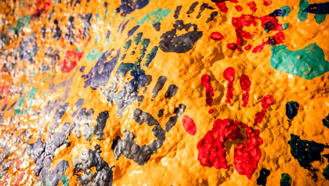 Hand prints cover The Rock on UT's campus during a gathering on Feb. 9 to speak out against recent racist messages painted on it.