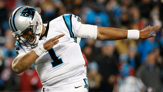 Carolina Panthers quarterback Cam Newton (1) dabs during the fourth quarter against the Arizona Cardinals in the NFC Championship football game at Bank of America Stadium.