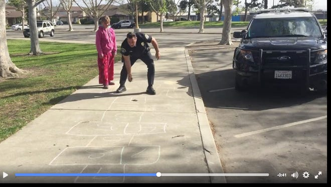 A California police officer playing hopscotch with an 11-year-old girl.