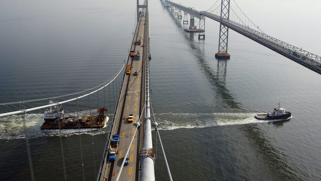 In this view, looking east from a tower of the westbound span of the Chesapeake Bay Bridge, a tugboat tows a barge south on the Chesapeake Bay on Jan. 30, 2002.