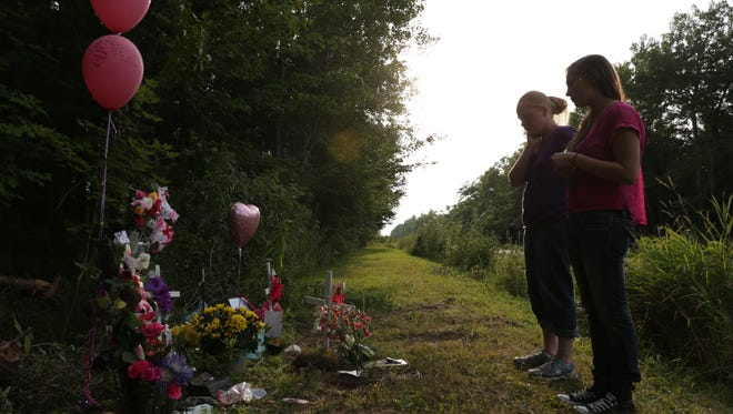 AuDena LaBarge, right, 16, and her mother Char LaBarge, both of Wausau, stop, Sunday, August 10, 2014, and pay their respects at a memorial set up for two children that died as a result of a one-vehicle crash this past Friday along Highway 52 northeast of Wausau. The LaBarges knew some of the 10 young people that were in the vehicle that crashed.
