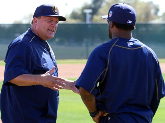 Brewers bench coach Pat Murphy, left, talks with Eric Young Jr.