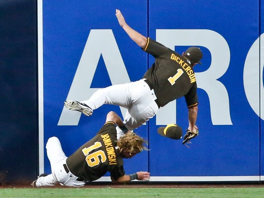 San Diego Padres left fielder Alex Dickerson, top, collides with center fielder Travis Jankowski while trying catch a ball hit by Cincinnati Reds' Zack Cozart during the first inning of a baseball game Friday, July 29, 2016, in San Diego. Cozart got a triple and Dickerson left the game. (AP Photo/Lenny Ignelzi)