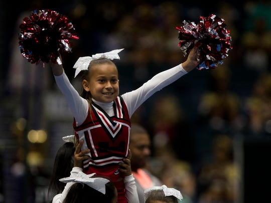 A little girl with Immokalee Pop Warner cheers during her squad's routine in the Peace River Conference Pop Warner Cheerleading Competition on Sunday, Oct. 22, 2017, in Estero, Fla. Teams throughout the region came to support their hometowns in the event.