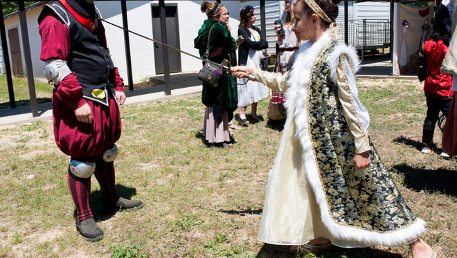 Gulf Breeze Elementary student Nerissa Williamson, right, learns about weaponry and sword play from Brad Cramer, left, of the University of West Florida Fencing Club, during the school's Medieval Fest Friday May 6, 2016.