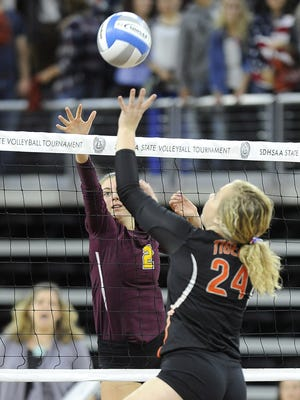 Harrisburg's #2 Madison Wassink attempts to block against Huron's #24 Karissa Schroder as she spikes the volleyball during state volleyball action at the Denny Sanford Premier Center in Sioux Falls, S.D., Thursday, Nov. 19, 2015.
