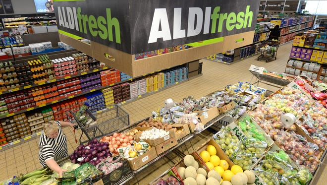 Customers shop at the Aldi grocery store at 6925 Durand Ave., Mount Pleasant. As one of the first of 23 stores being remodeled by the discount grocery chain, it has new signage in the produce area.
