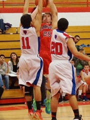 Senior Sam Brown attempts to shot the ball as Estancia's players defend the basket.