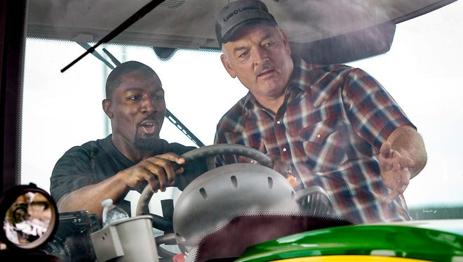 Former Minnesota Vikings wide receiver Greg Jennings learns to drive a tractor for the Land O'Lakes Farm Bowl from Marvin Carrow at the Enchanted Dairy on Sunday, July 23, in Little Falls.