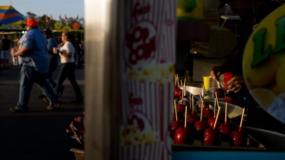Shortly after the gates open and the sun begins to set a caramel apple vendor prepares for the rush of hungry spectators at the Collier County Fair Monday, March 19, 2018 in Naples.