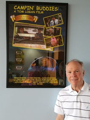 """Tom Logan, director of """"Campin' Buddies,"""" stands with his movie poster at the Shreveport Regional Airport."""