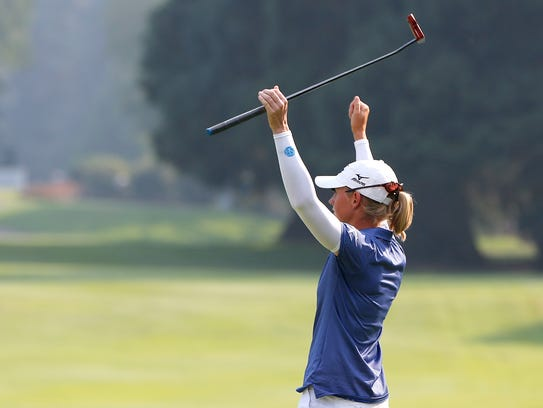 Stacy Lewis celebrates on the 18th green after her
