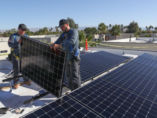 Renova Solar technicians Jeff Flores, left, and Luis Banuelos install solar panels on a Palm Springs home on Feb. 6, 2018.
