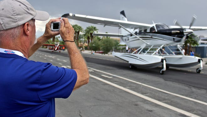 An attendee snaps a photograph of an aircraft during the Parade of Planes on Thursday. Airplanes taxied from the Palm Springs International Airport to the Palm Springs Convention Center as a kickoff event for the Flying Aviation Expo.