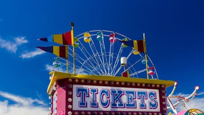 Ticket booth and Carnival Rides at a Fair on sunny day.