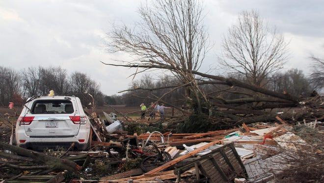 """Neighbors inspect the remains of a storm-damaged home in the Roundaway community near Clarksdale, Miss., Wednesday, Dec. 23, 2015. A storm system forecasters called """"particularly dangerous"""" killed multiple people as it swept across the country Wednesday. (Troy Catchings/The Press Register via AP) MANDATORY CREDIT"""