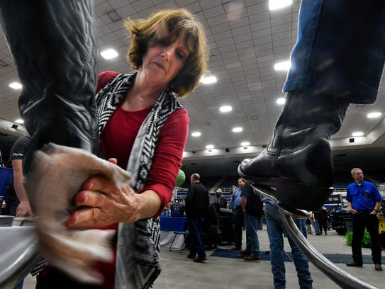 Becky Hall shines the boots of Comanche's Bill Taylor at the T & W Tire of Wichita Falls booth during Tuesday's Texas Farm-Ranch-Wildlife Expo at the Taylor County Coliseum Feb. 20, 2018. The show continues Wednesday.