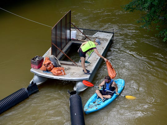 AmeriCorps member Lillian Lovegood, left, tosses bags of trash into Asheville GreenWorks director of operations Eric Bradford's boat so he can paddle it to shore after cleaning out the trash trout they have installed in Mud Creek in Hendersonville on Friday, June 14, 2017.