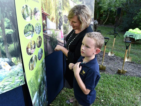 Susan Adams, and her son James Henry Davey, 7, both of Vero Beach, look over renderings of the planned new Children's Garden at McKee Botanical Garden before the start of the groundbreaking Nov. 8, 2017. The approximate 1-acre addition  will feature an Interactive children's garden with a water play area, a reading circle and a pirate ship.