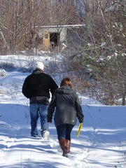 Staff from Harmony House and Volunteers of America investigate an abandoned trailer located behind a McDonald's billboard at Ohio 545 and U.S. 30. No squatters were found in the area, but staff did see footsteps in the snow leading up to the structure.