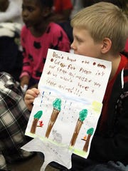 Cam'Ren McKay, 10, a fourth-grader at McVey Elementary School in Newark, on Monday holds a sign asking Delaware lawmakers to reject allowing hunting of the gray fox.