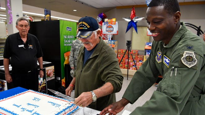 Bruce Griffin, who served with the U.S. Air Force in Vietnam from 1966-67, helps 7th Bomb Wing Commander Brandon Parker cut a cake honoring veterans from the Vietnam War Thursday. The Dyess Air Force Base Commissary and base exchange offered lapel pins, badges, and other items to Vietnam veterans Thursday as they came in to shop.