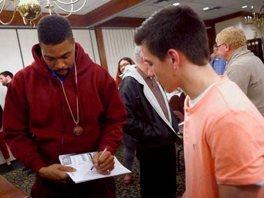 Columbus basketball legend Estaban Weaver signs an autograph for Christian Durbin after speaking at Wednesday night's banquet honoring the participants in Thursday night's 38th News Journall All-Star Classic at Der Dutchman Restaurant in Bellville.