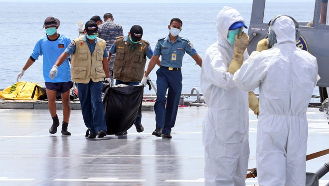 Crew members carry a bag containing the body believed to be a victim of AirAsia Flight 8501 to a waiting helicopter on the deck of Indonesian Navy ship KRI Banda Aceh, on the Java Sea, Indonesia, Friday, Jan. 23, 2015.