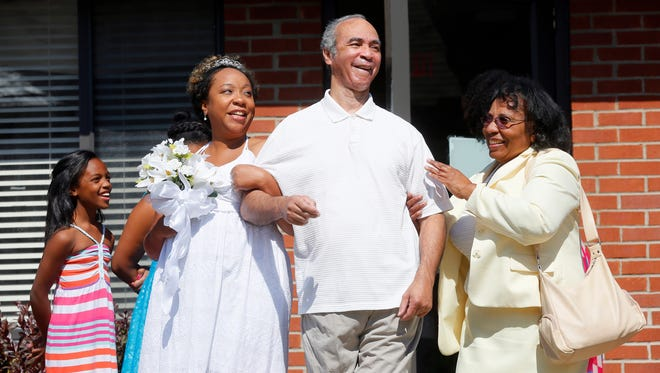 Miriam Reeves is escorted down the aisle by her father  Bernard Reeves, 64, who has Alzheimer's, and her mother Marie Reeves, right, during the Reeves / Davis wedding at Foundation Park Alzheimer's Care in Toledo, Ohio, Saturday, Aug. 16, 2014. Reeves wanted the ceremony to take place beneath the gazebo in the courtyard of the facility so that her father could participate in the happy affair. Niece Autumn Reeves, 8, left, watches.