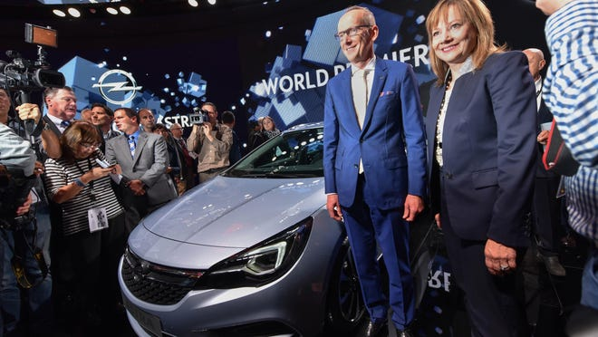 CEO of Opel Karl-Thomas Neumann, left, and Mary Barra, CEO of General Motors, right, present the new Astra Sports Tourer at the Frankfurt Auto Show IAA in Frankfurt, Germany, Tuesday, Sept. 15, 2015. The car show runs through Sept. 27. (Uwe Zucchi/dpa via AP)