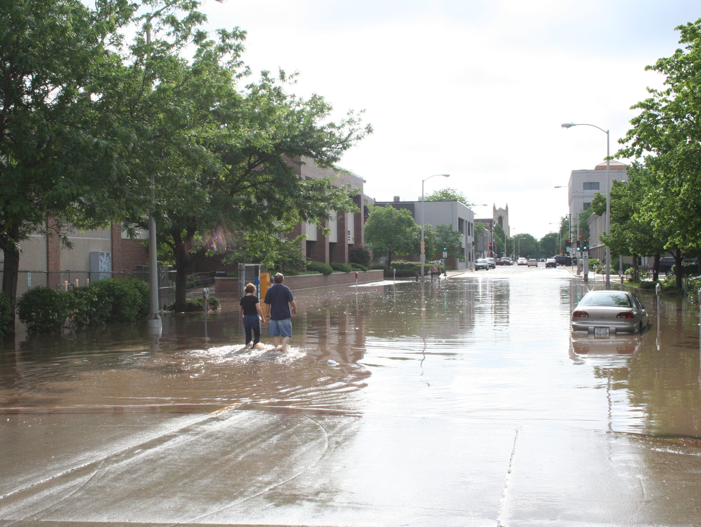 People wade through the flood waters on West Second